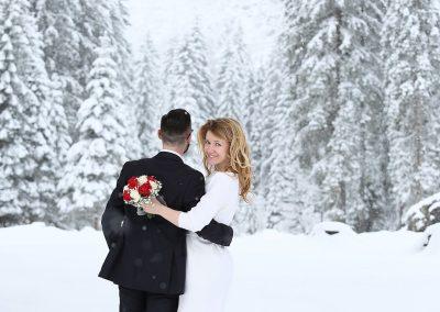 Fotografia sposi sulla neve in montagna con abito corto