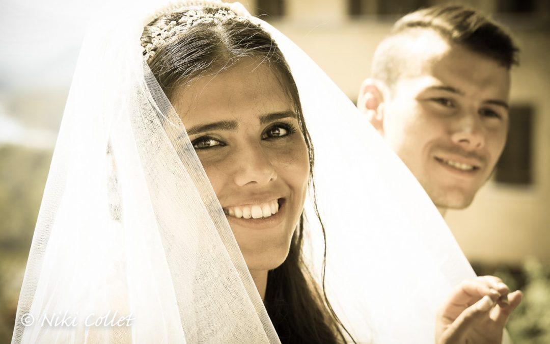 Una sposa sorridente e lo sposo al suo fianco